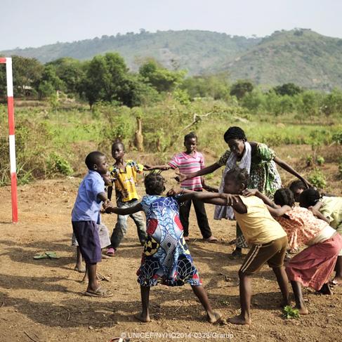 Unos niños y su maestra juegan al aire libre en círculo en República Centroafricana
