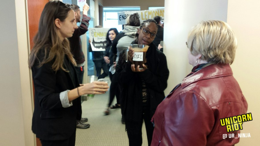 "Community members, water protectors offer cups of ""oil"" to Enbridge employees"