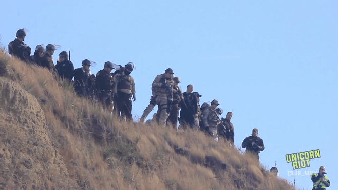 "Police standing on sacred burial grounds on ""Turtle Island"" land formation in Cantapeta Creek"
