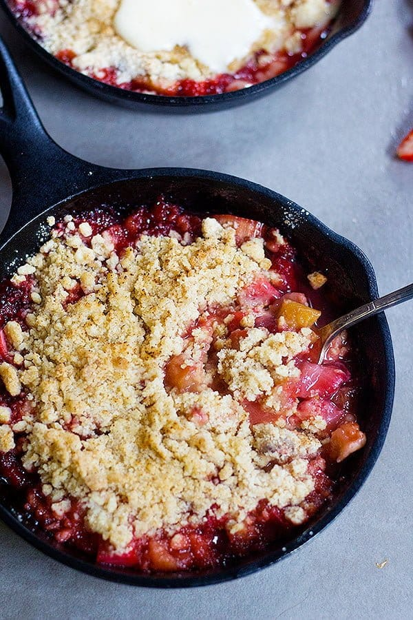 strawberry rhubarb crumble made in small cast iron skillets with a buttery crumble on top.