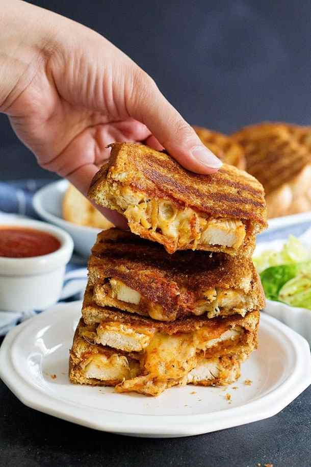 Grilled cheese chicken parmesan sandwich is the best of both worlds! Delicious chicken smothered in tomato sauce, pressed between two slices of bread with a lot of cheese!