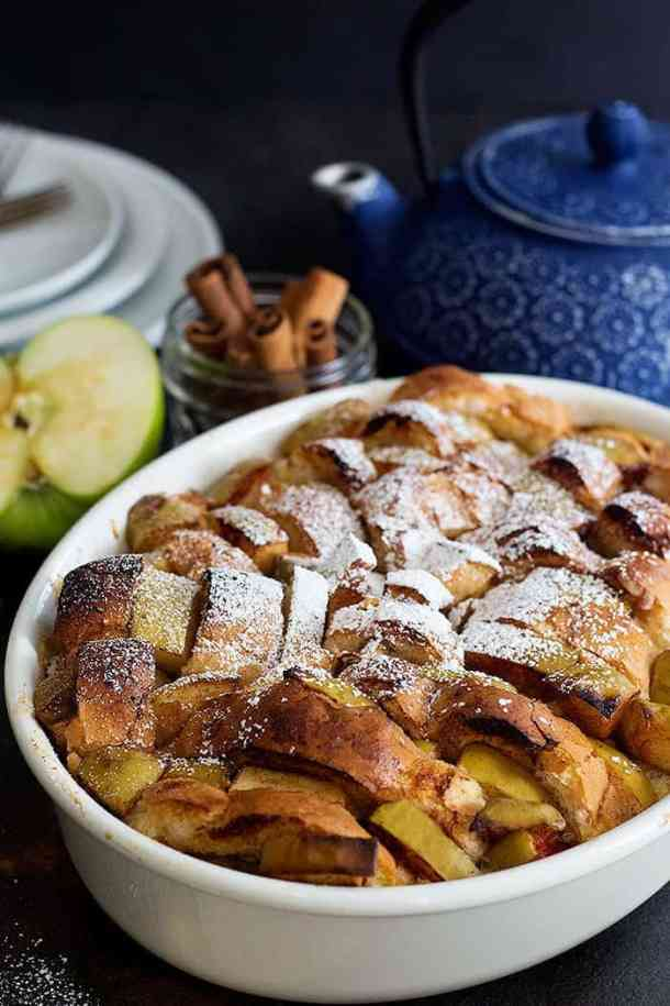 slices of baked bread with apples and cinnamon topped with powdered sugar.