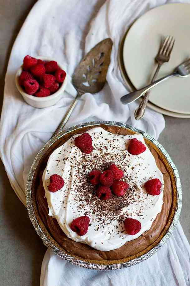 no bake chocolate cream pie topped with whipped cream and raspberries
