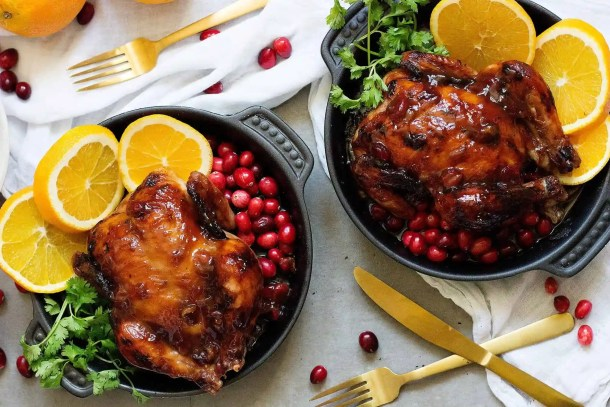 Orange Glazed Cornish Hens with orange slices and greens for the holidays.