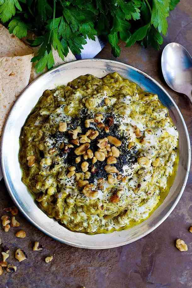 The toppings for this Persian eggplant dip are kashk, sauteed mint and walnuts.
