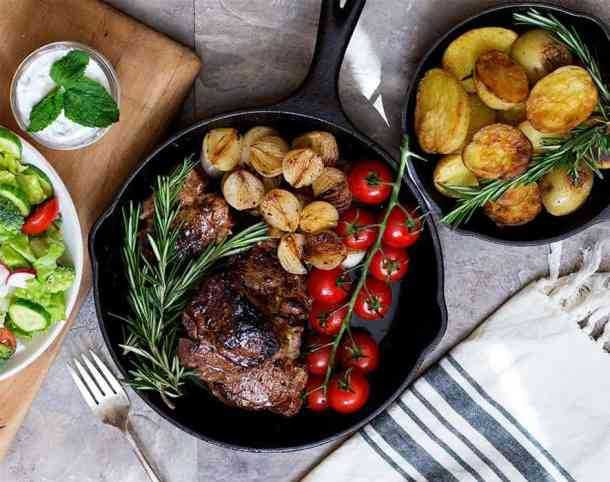 Lamb loin chops served with potatoes and salad.