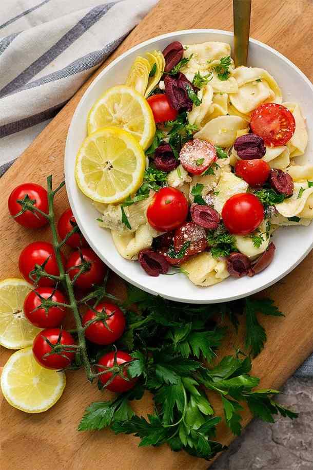 tortellini pasta salad is a delicious side for summer parties served with lemon parsley and fresh tomatoes.