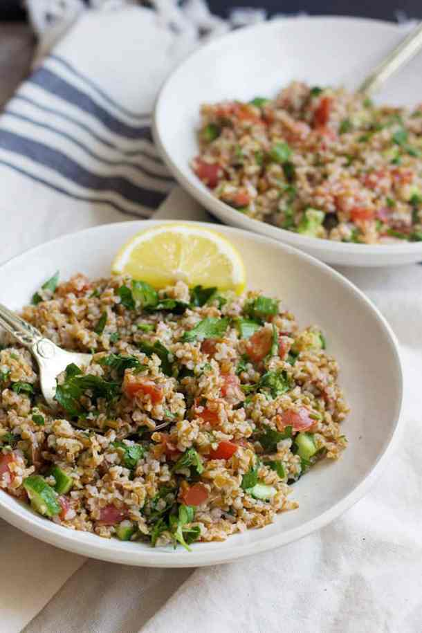 Serve tabbouleh salad in bowls with a slice of lemon.
