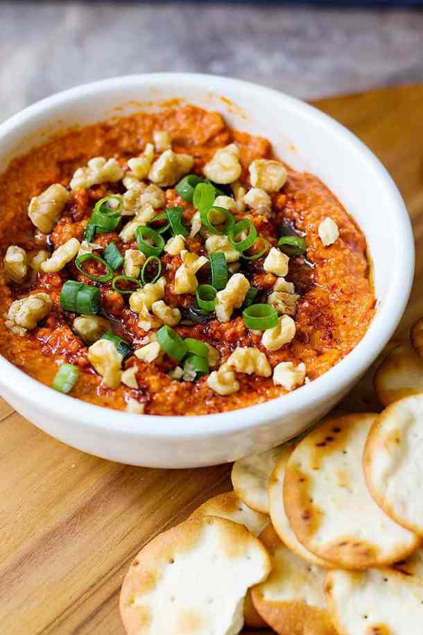 Muhammara dip or red pepper dip topped with walnuts and green onion.