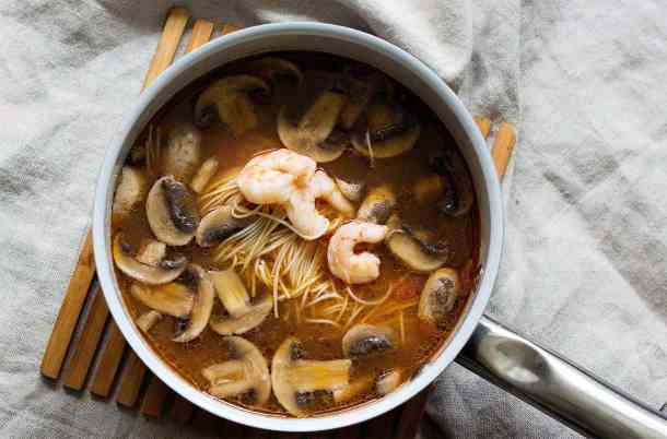 Add in shrimp, noodles and mushrooms to the spicy ramen soup and cook for about 5 minutes.