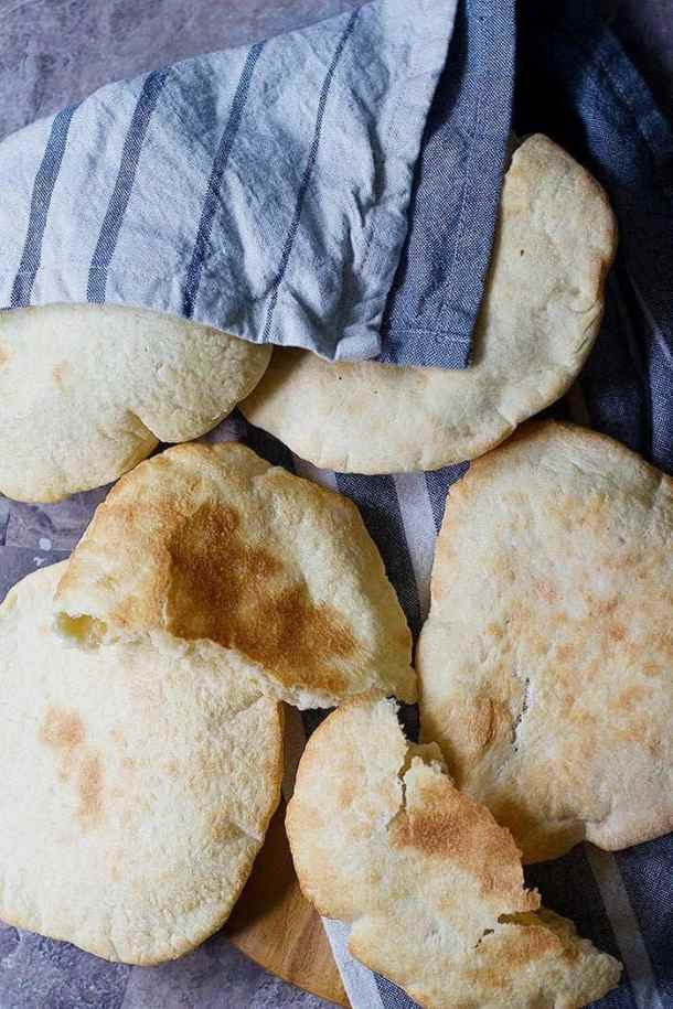 A few pita breads on a surface with a kitchen towel on two of them.
