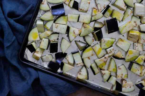 To roast eggplants for caponata: Cut the eggplants into cubes and place them on the baking sheet. Drizzle with olive oil and sprinkle some salt.