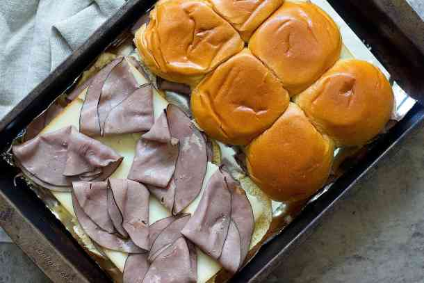Place the bottoms in a 9x13 baking pan or on a baking sheet lined with aluminum foil. Spread a little bit of the melted butter mixture on the rolls. Top with half of the roast beef and then top with cheese. Add another layer of roast beef and finish with the top layer of the Hawaiian rolls.