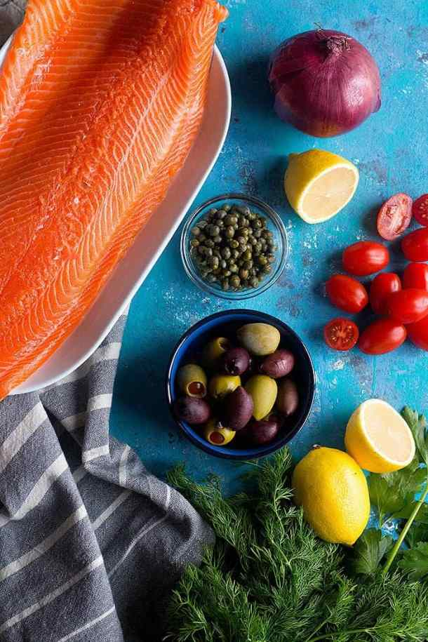 To make baked salmon, you need a side of salmon, olives, lemon, onion and tomatoes