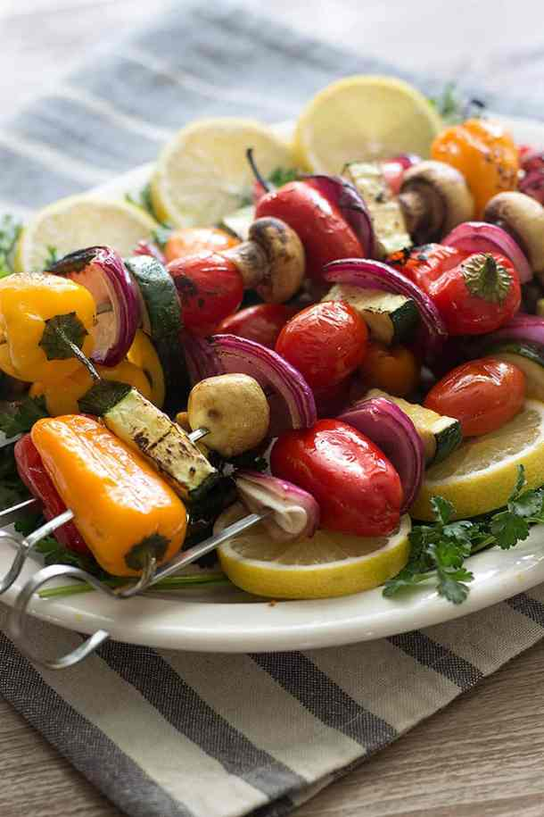 vegetable kabob is made with peppers, zucchini, tomatoes, mushrooms and onion.