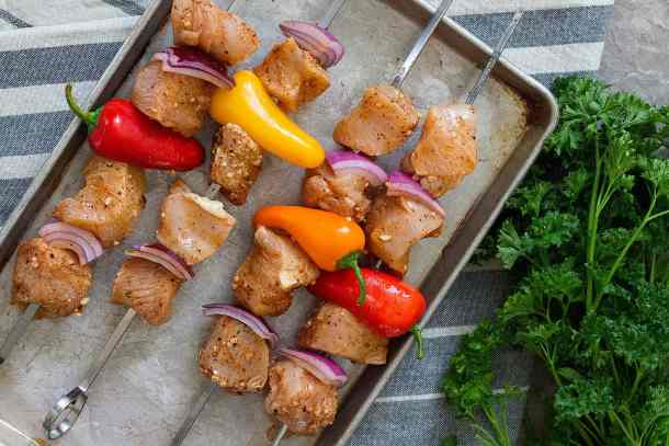 Thread marinated chicken on the skewers and start grilling.