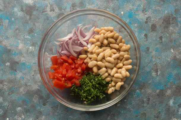 To make white bean salad mix beans tomato parsley and onions in a large bowl