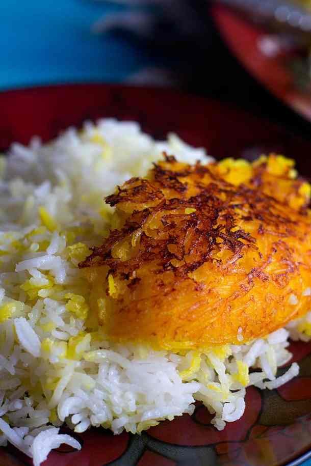 Tahdig on white and saffron rice on a red plate