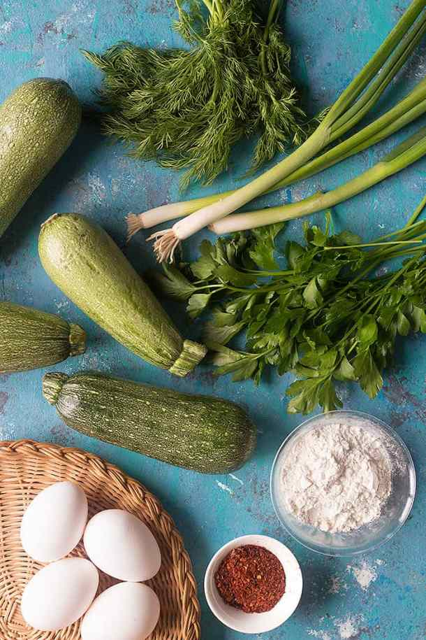 To make zucchini fritters you need zucchinis, green onion, parsley, dill, eggs, flour and Aleppo pepper.