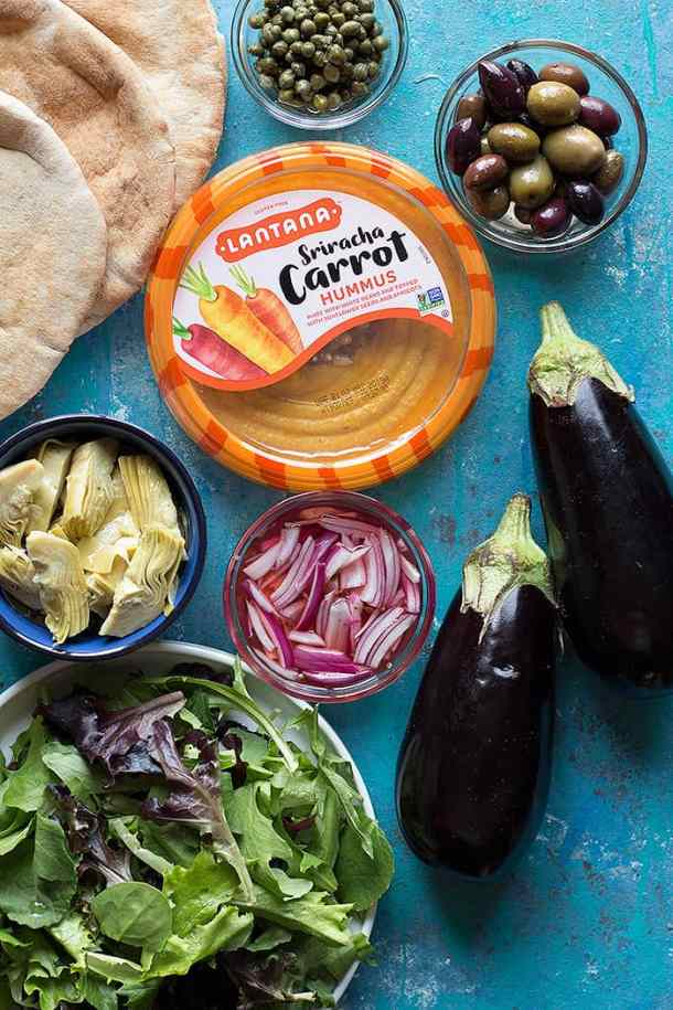 to make grilled eggplant sandwich you need pita bread, eggplants, hummus, olives, greens, artichokes, capers and onions.