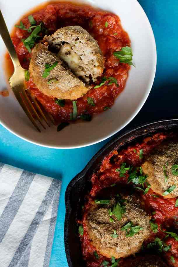 big meatball cut in half in a bowl with tomato sauce.