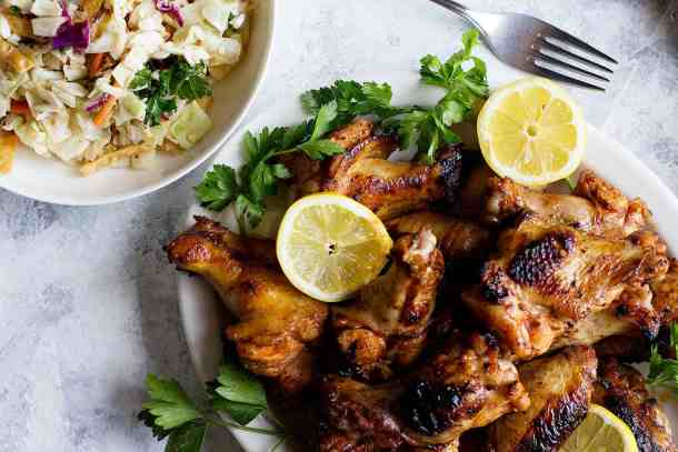 Overhead shot of chicken wings topped with lemon with a side salad.