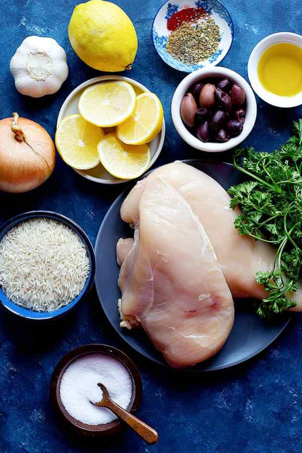 Ingredients to make Greek one pan chicken and rice are chicken rice lemon spices olives onion and garlic