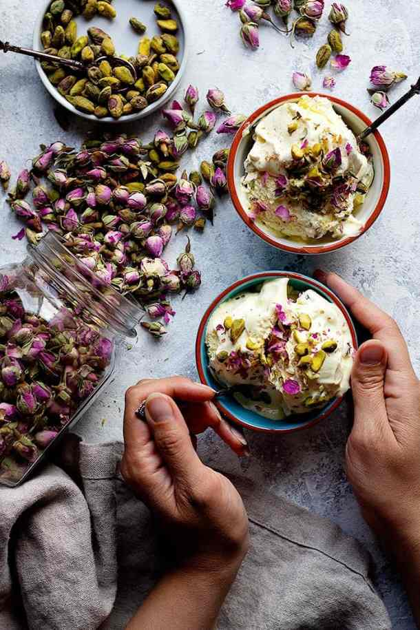 Two bowls of Persian ice cream with roses and pistachios.