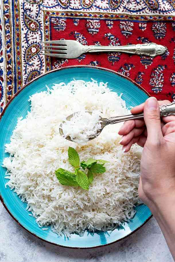 a blue plate full of rice topped with fresh mint.