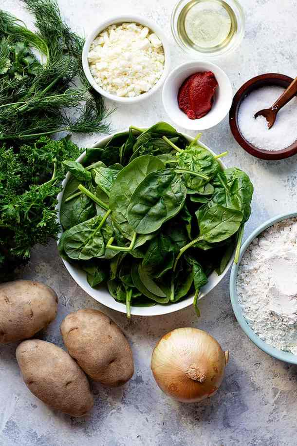 to make turkish flatbread you need potatoes, spinach, flour, oil, cheese, greens and tomato paste.