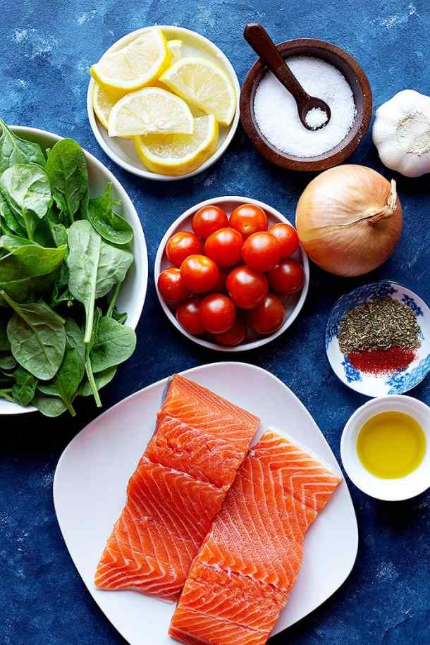 this recipe is made with salmon, lemon, spices, salt, onion, garlic, olive oil, lemon juice, spinach and tomatoes.