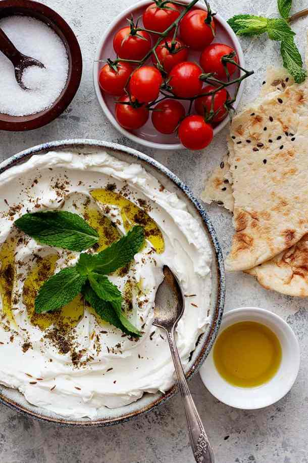 Labneh spread in a shallow bowl served with pita.