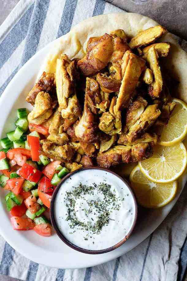chicken shawarma is a delicious Mediterranean recipe that's served with pita, tomatoes, cucumbers and yogurt.