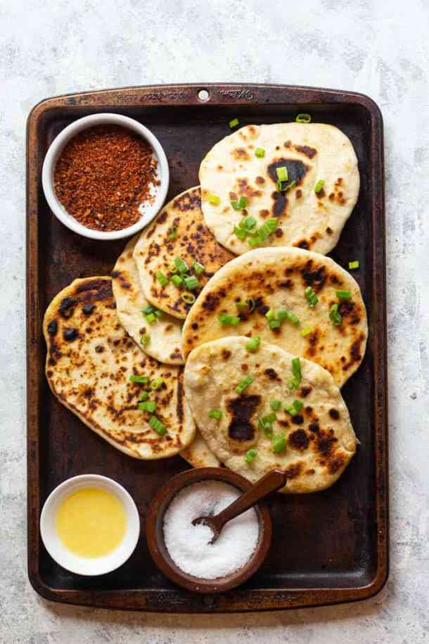 naan is brushed with ghee and topped with green onion.
