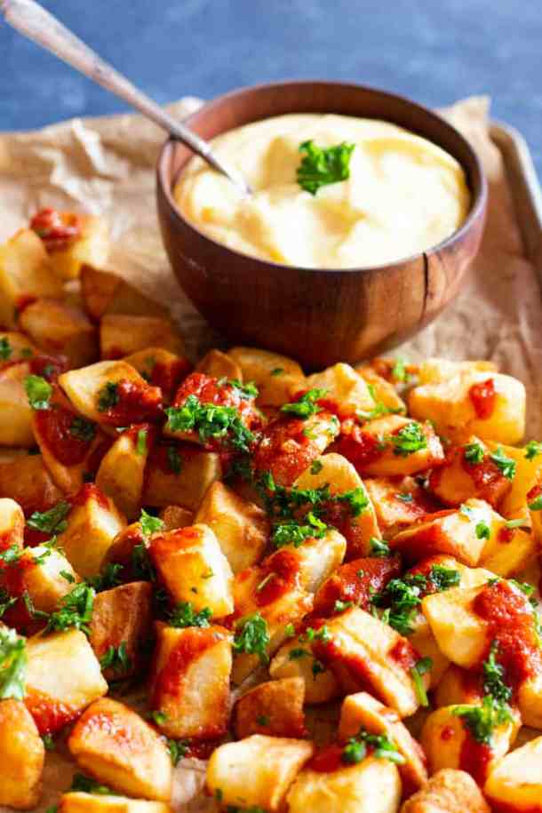 Patatas bravas is a Spanish dish and is usually served with aioli sauce and a red sauce.