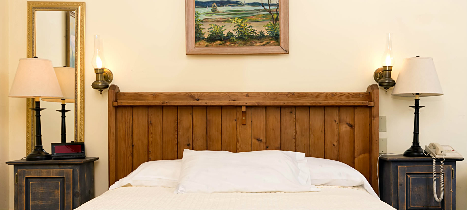 A whte bed with a pillow and a brown wooden headboard sits between two small tables with lamps