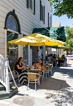 Rows of white and yellow tables and chairs with yellow umbrellas line the sidewalk outide the old building