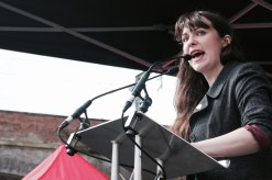 Photograph of Amelia Womak (Deputy Leader, Green Party) addressing NO MORE AUSTERITY demonstrators at Castle Arena, Manchester.
