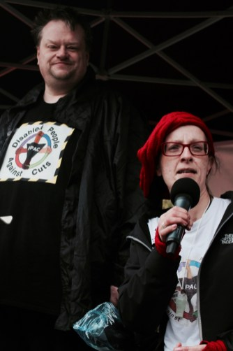 Photograph of Rick Burgess and Dennis Queen (Disabled People Against Cuts (DPAC)) addressing NO MORE AUSTERITY demonstrators at Castle Arena, Manchester.