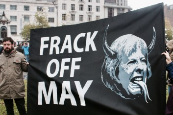 """Photograph of NO MORE AUSTERITY demonstrator holding """"FRACK OFF MAY"""" placard at Piccadilly Gardens, Manchester. 1st October 2017."""