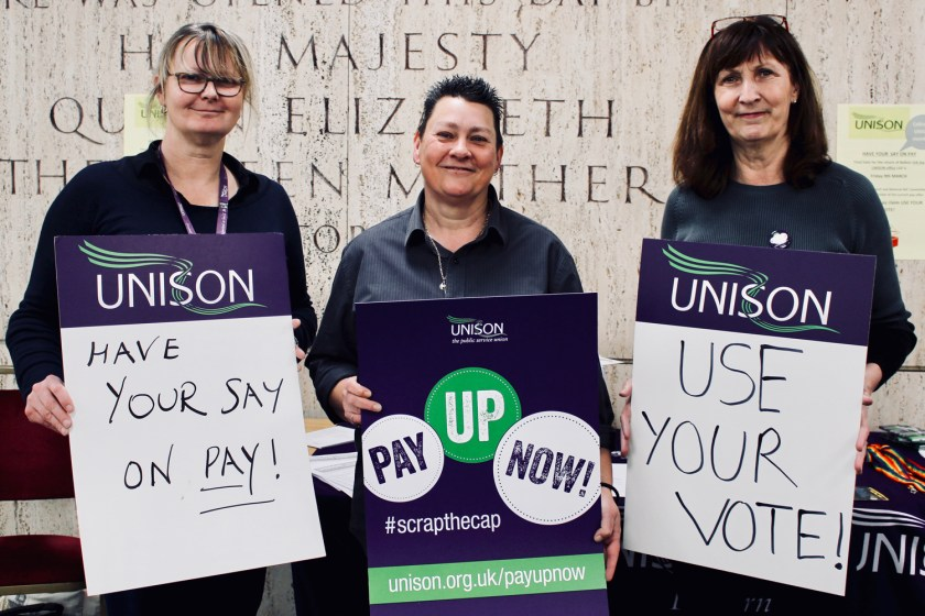 Photograph of Claire Wormald (Branch Secretary), Sam Adams (LGBT+ Officer) and Kate Stafford (Local Organiser, UNISON Eastern) on the UNISON Pay Up Now! campaign stall on 6th February at the Civic Centre Foyer, Southend Borough Council. They are holding placards reading: HAVE YOUR SAY ON PAY! PAY UP NOW! and USE YOUR VOTE!