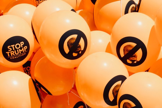 Photograph of a cluster of orange balloons with the following printed in black: 'STOP TRUMP Coalition' slogans and prohibitive circles signs with diagonal bars superimposed over Donald Trump's face.