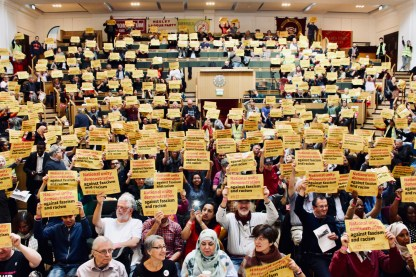 Photograph of attendees at STAND UP TO RACISM International Conference 2018 holding National Unity Demonstration posters above their heads as a sign of support.