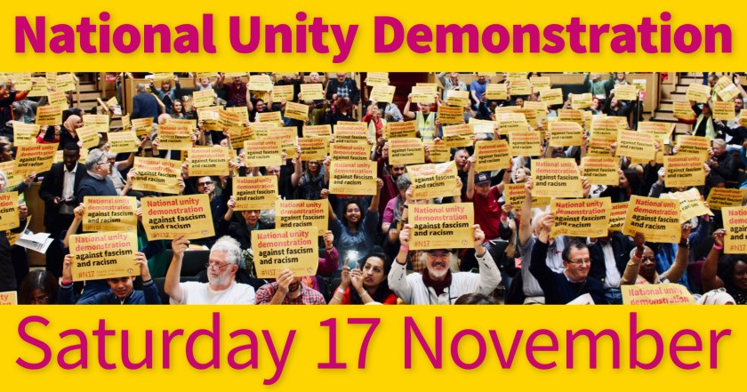 "Photograph showing a large group of STAND UP TO RACISM International Conference attendees holding National Unity Demonstration posters above their heads as a sign of support – the accompanying text reads: ""National Unity Demonstration Saturday 17 November."""