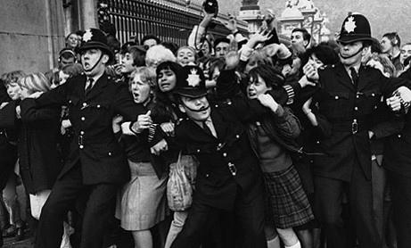 Imagen de una masa de fans de los Beatles intentando ser contenida por la policía [Foto vía 50añosdebeatlemanía].