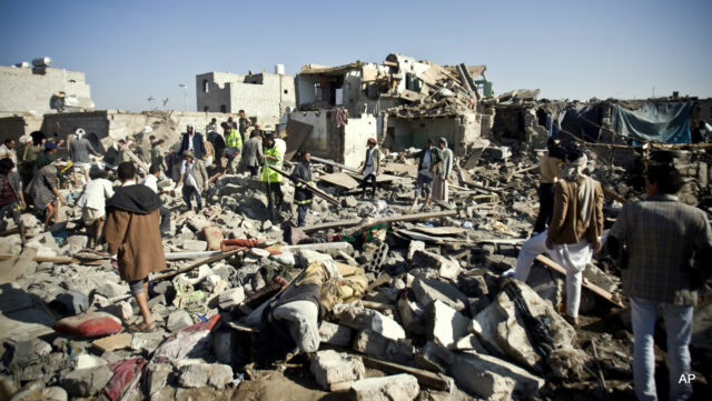 People search for survivors under the rubble of houses destroyed by Saudi airstrikes near Sanaa Airport, Yemen, Thursday, March 26, 2015. Saudi Arabia launched airstrikes Thursday targeting military installations in Yemen held by Shiite rebels who were taking over a key port city in the country's south and had driven the embattled president to flee by sea, security officials said. (AP Photo/Hani Mohammed)