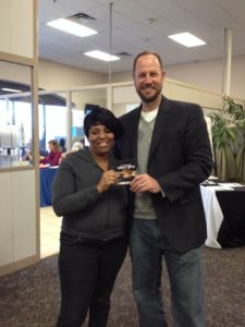 United Way RealSense Director Jeff Winkler presents Ophelia Webb with a gas card door prize during the RealSense Super Saturday event Feb. 14.  Webb completed her taxes for free at the Gateway Mall CareerSource site and plans to put her tax refund toward starting her own business.