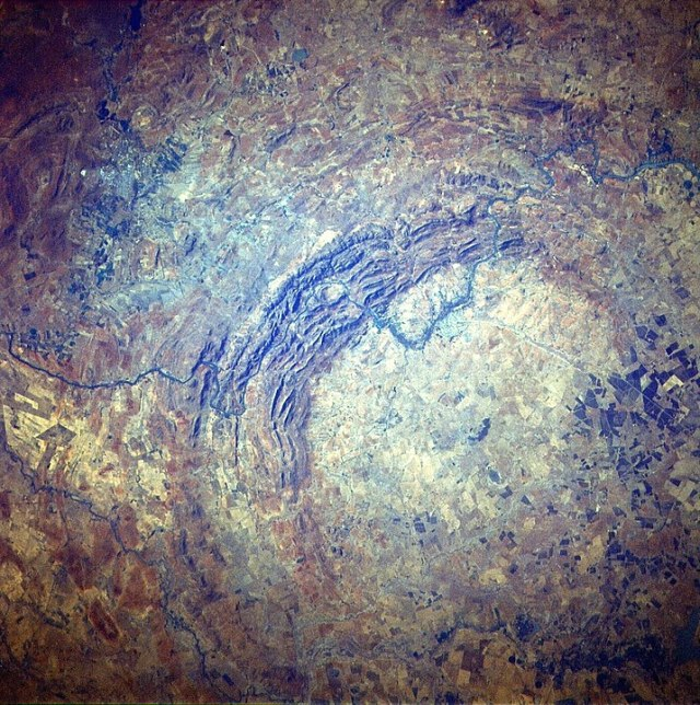 The Vredefort crater dome as seen from space on the STS-51-I mission. It was created by the impact of a large object about two billion years ago. The new research letter claims it could be the result of a long-period comet ripped apart by the Sun's tidal forces, with one of the fragments striking Earth. By Júlio Reis (User:Tintazul) - [1], Public Domain, https://commons.wikimedia.org/w/index.php?curid=400487