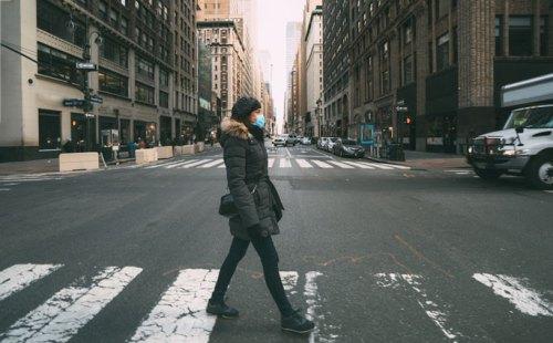 Woman walks down empty city street wearing a mask