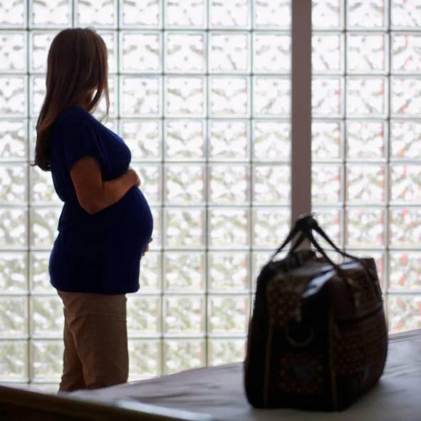 Donna incinta in ospedale e valigia in primo piano